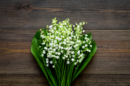 Photo pour May flowers. Bouquet of lily of the valley flowers on dark wooden background top view copy space - image libre de droit
