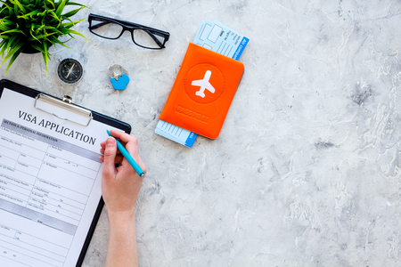 Photo pour Hand fills visa application form. Form near glasses, pen, passport cover with airplane sign and airplane tickets on grey background top view. - image libre de droit