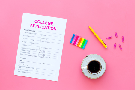 Higher education. College application form ready to fill near coffee cup and stationery on pink background top view