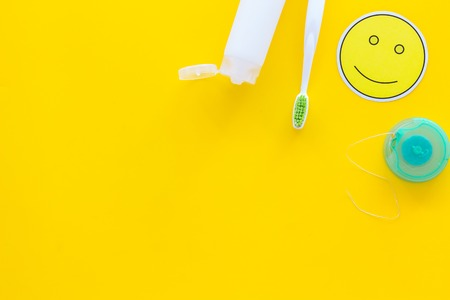 Photo pour Set for daily teeth care. Toothbrush, tooth paste, dental floss on yellow background top view copy space - image libre de droit