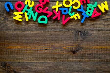 Foto de Alphabet for kids concept. English letters in disorder on dark wooden background top view copy space - Imagen libre de derechos