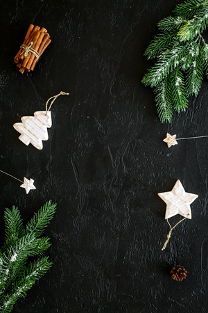 Foto de Decoration for winter holidays concept. Christmas, New year. Spruce branch, cones and toys on black background top view. - Imagen libre de derechos