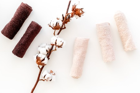 Photo pour Cotton towels high quality. Set of towels twisted coil near dry cotton flowers on white background top view. - image libre de droit