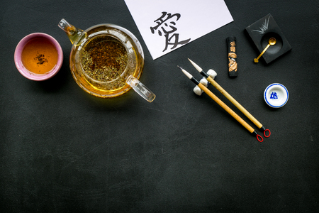 Photo pour Chinese or Japanese traditions. Calligraphy and tea ceremony concept. Special writing pen, ink near teapot and cup of tea, hieroglyph love on black background top view copy space - image libre de droit