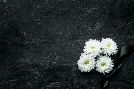 Photo pour Funeral symbols. White flower near black ribbon on black background top view space for text - image libre de droit