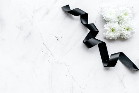 Photo pour Funeral symbols. White flower near black ribbon on white stone background top view copy space - image libre de droit