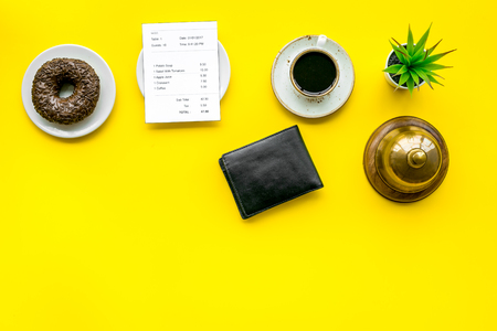 Foto per Pay the bill, pay at restaurant. Check near wallet, service bell, coffee on yellow background top view space for text - Immagine Royalty Free