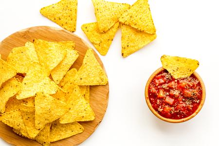 Foto de Snack for party. Mexican nachos near salsa sause on white background top view - Imagen libre de derechos