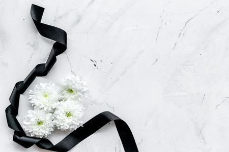 Photo pour White flower near black ribbon on white stone background - image libre de droit