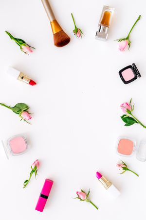 Photo pour Lipstick, bulk, eyeshadow and small rose flowers on white background - image libre de droit