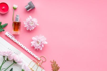 Foto de Perfume near notebook for dairy among flowers on pink background top view. - Imagen libre de derechos