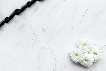 Foto de Funeral symbols. White flower near black ribbon on white stone background top view. - Imagen libre de derechos