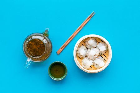 Chinese food set with dim sum, sticks and tea on blue background top view