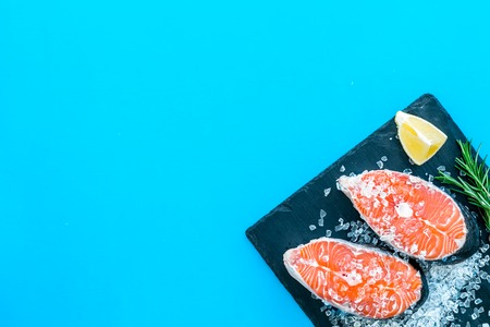 Cooking salmon steak from raw fish on black plate with rosemary on blue restaurant kitchen table background top view copy space