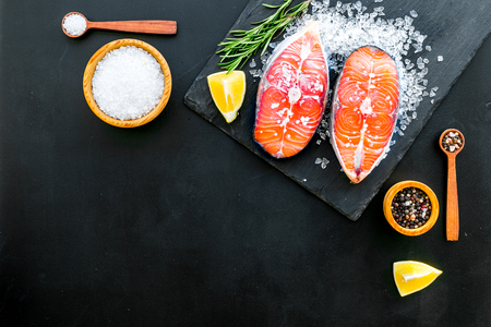 Fresh salmon steak with spices, rosemary, lemon for cooking healthy food on dark background top view mock-up