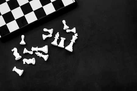 Photo pour Symbol of competition. Chess board and chess figures on black background top view space for text - image libre de droit