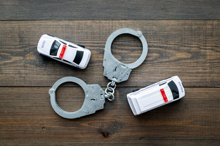 Police concept. Police car toy and handcuff on dark wooden background top view