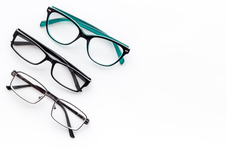Set of glasses with transparent lenses on white background top view space for text