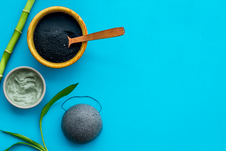 Photo for Face care. Cosmetics based on bamboo charcoal powder on blue background top view space for text - Royalty Free Image