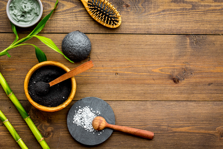 Photo for Skin cleansing and detox. Bamboo charcoal powder cosmetics on dark wooden background top view space for text - Royalty Free Image