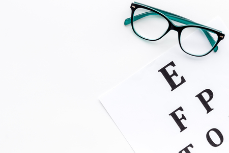 Foto de Eye examination. Eyesight test chart and glasses on white background top view. - Imagen libre de derechos