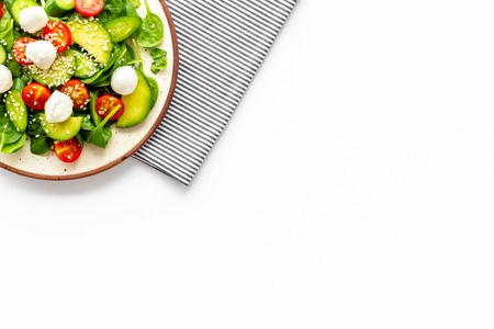 Photo pour Fresh salad with mozzarella, spinach, cherry tomatoes, cucumber on plate on white background top view space for text - image libre de droit