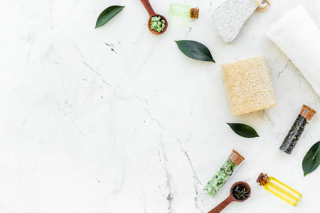 Foto de Tea tree spa composition. Fresh tea tree leaves, natural cosmetics, towel on white stone background top view copy space border - Imagen libre de derechos