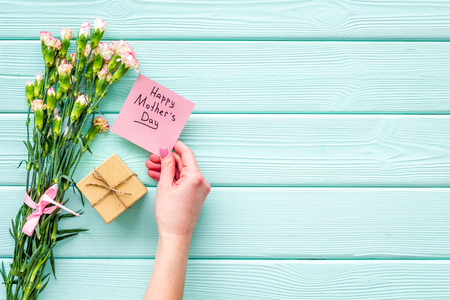 Foto de Happy Mother's Day concept. Hand lettering near bouquet of pink carnation and gift box on blue turquoise wooden background top view. - Imagen libre de derechos