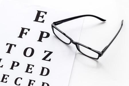 Photo for Eye examination. Eyesight test chart and glasses on white background - Royalty Free Image