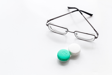 Foto de Eye problems. Glasses with transparent lenses and contact lenses on white background space for text - Imagen libre de derechos