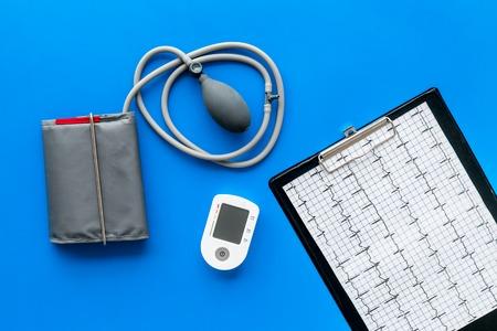 Tonometer cardiogram for heart diseases diagnostic on blue desk background top view