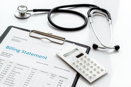 Photo pour Medical treatment bill, calculator and phonendoscope on white desk background - image libre de droit