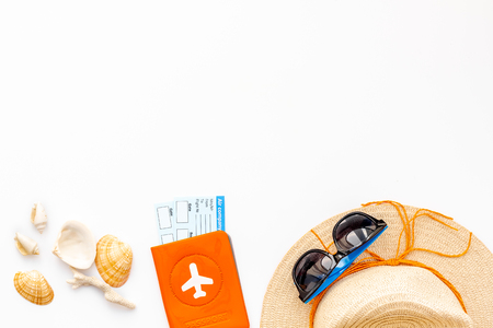 Photo pour Straw hat, sun glasses, passport with tickets, shells for sea vacation on white background top view mockup - image libre de droit