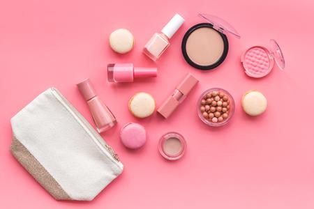 Foto de Beauty blogger work. Make-up artist desk with nude powder, nail polish, lipstick, blusher, bag, decorative cosmetics and macaroon cookies on pink background top view - Imagen libre de derechos