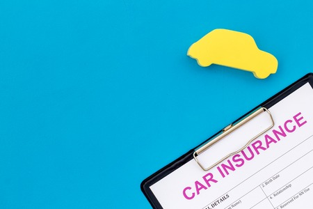 Photo pour Car buying and insurance concept with car figure and form on blue desk background top view mock up - image libre de droit