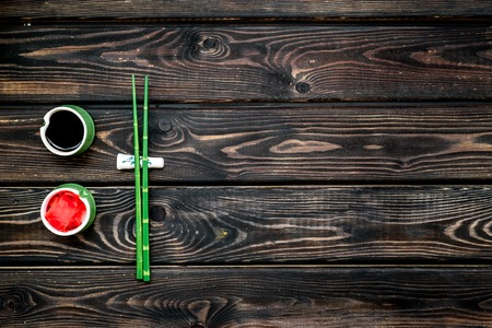 Foto de Oriental table set up. Japanese food cooking set with soy sauce, ginger, bamboo sticks for sushi or maki on wooden background top view copy space - Imagen libre de derechos