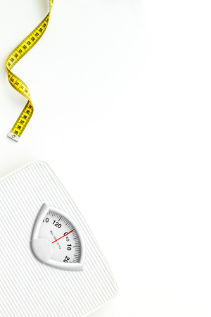 Photo pour Diet. Bathroom scales and measuring tape for weight loss concept on white background top view space for text - image libre de droit