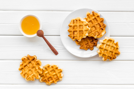 Foto de Sweet snack. Viennese waffles. Homemade Belgian waffles with honey on served table on white wooden background top view - Imagen libre de derechos