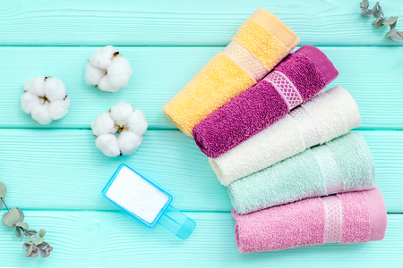 Foto de Products of cotton set. Preparing for laundry with washing powder and towels on mint green wooden background top view - Imagen libre de derechos