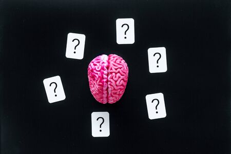 Discussion in office. Brain storm and business ideas concept with brain and question mark on black background top view