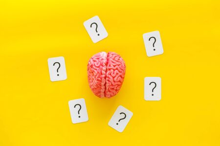 Discussion in office. Brain storm and business ideas concept with brain and question mark on yellow background top view