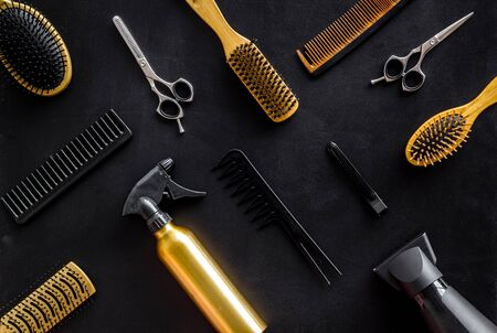 Photo pour Combs, scissors and hairdresser tools in beauty salon work desk on black background top view pattern - image libre de droit
