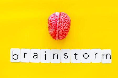 Discussion in office. Brain storm and business ideas concept with brain on yellow background top view