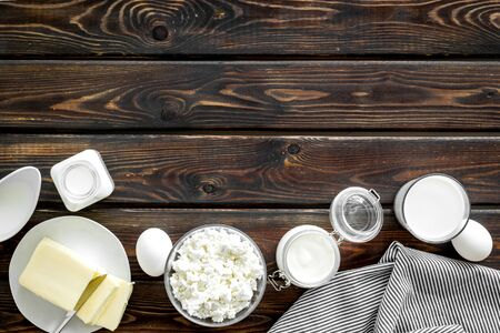 Dairy products from farm with milk, eggs, cottage, butter, yogurt on wooden background top view mockup