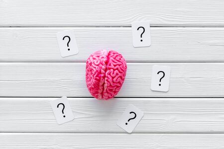 Discussion in office. Brain storm and business ideas concept with brain and question mark on white wooden background top view