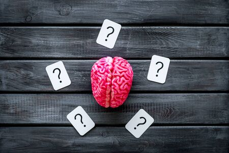 Brain storm and business ideas concept with brain and question mark on wooden background top view