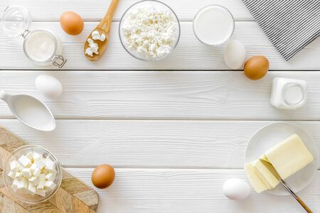 Dairy products from farm with milk, eggs, cottage, butter, yogurt frame on white wooden background top view mockup