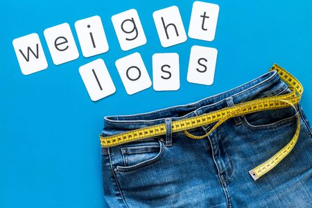 Photo pour Weight loss text with jeans and measuring tape on blue background top view - image libre de droit