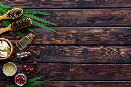 Foto de Bottle with jojoba, argan or coconut oil, styling, comb for hair style on wooden background top view mock up. - Imagen libre de derechos