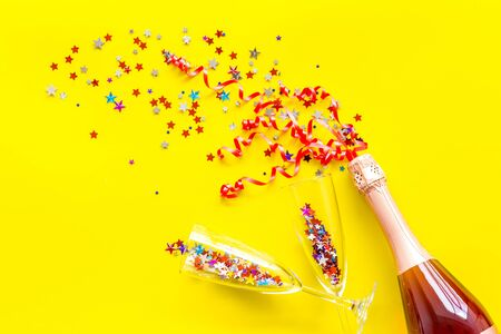 Foto de Party with champagne bottle, glasses and colorful party streamers on yellow background top view - Imagen libre de derechos